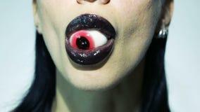 Horror concept - Beautiful Sexy Stylish Woman eating Red Eye. Horror psychedelic concept - Beautiful Sexy Stylish Woman Eating Red Eye and licking her dark lips stock footage