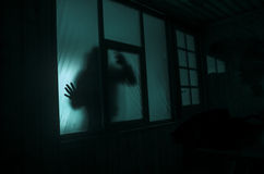 Horror concept. The silhouette of a human with sprayed arms in front of a window. at night. Stock Images