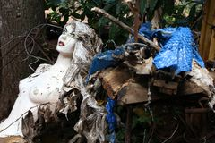 Horror. Creepy mannequin doll in an illegal garbage dump. Old manequin - mysterious horror atmosphere royalty free stock photography