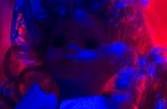 Horror doll blue & red light. Stock Photos