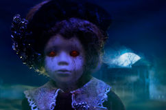 Horror doll with haunted house. Old mystical scary horror doll looking with red demonic eyes with haunted horror house royalty free stock images