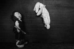 Horror doll holding knife. Horror doll murder hanging another in white tone with shadow edge Stock Image