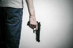 Horror and firearms topic: crazed killer with a gun on a gray background in the studio. Horror and firearms topic: crazed killer with a gun on a gray background Stock Photo