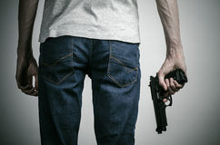 Horror and firearms topic: crazed killer with a gun on a gray background in the studio Stock Photo