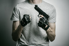 Horror and firearms topic: the killer with a gun in his hand in black gloves on a gray background in the studio Stock Photography