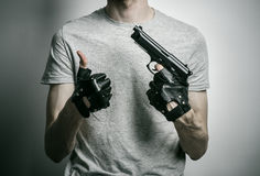 Horror and firearms topic: the killer with a gun in his hand in black gloves on a gray background in the studio Stock Photos
