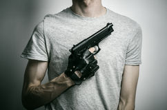 Horror and firearms topic: the killer with a gun in his hand in black gloves on a gray background in the studio Stock Photo