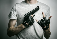 Horror and firearms topic: the killer with a gun in his hand in black gloves on a gray background in the studio Royalty Free Stock Photography