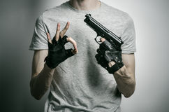 Horror and firearms topic: the killer with a gun in his hand in black gloves on a gray background in the studio Royalty Free Stock Images