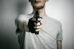 Horror and firearms topic: the killer with a gun in his hand in black gloves on a gray background in the studio Royalty Free Stock Photo