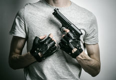 Horror and firearms topic: the killer with a gun in his hand in black gloves on a gray background in the studio Stock Image