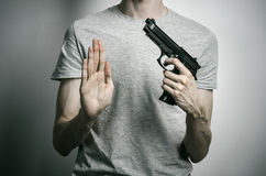 Horror and firearms topic: suicide with a gun on a gray background in the studio Stock Images