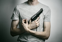 Horror and firearms topic: suicide with a gun on a gray background in the studio Royalty Free Stock Photo