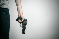 Horror and firearms topic: suicide with a gun on a gray background in the studio Stock Photos