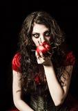 Horror geschossen: merkwürdiges furchtsames Mädchen isst den Apfel, der mit Nägeln verziert wird Stockbild