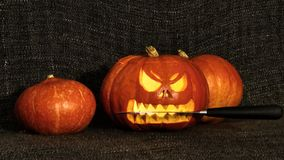 Horror halloween pumpkin with a knife in the mouth. Scary halloween pumpkin with a knife in the mouth Stock Photos