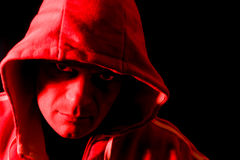 Horror hoodlum. Horror portrait of a hooded man, lit by a red strobe from the side Stock Photos