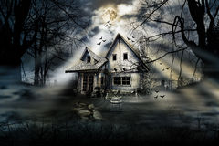Horror House. Haunted house with dark scary horror atmosphere around it.Dark cloudy sky, trees silhouettes and bats coming out of the windows