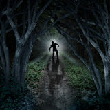 Horror Monster Walking. In a dark forest as a scary fantasy concept with a creepy thing coming out of a remote wilderness background with a moon glow behind it Royalty Free Stock Image