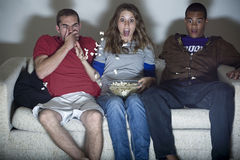 Horror Movie. Three people expressing fear as they watch a horror movie Stock Image