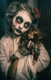 Horror movie scene. Of a scary woman with bloody doll Royalty Free Stock Images