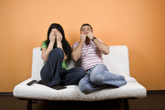 Horror movie at TV. Couple watching TV a horror movie,woman cover eyes to not see anymore  while the young man are terrified,check also Couples Stock Photo