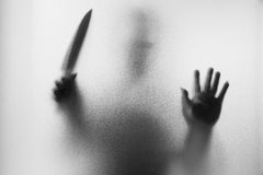 Horror Murderer. Dangerous man behind the frosted glass with a k. Nife on his hand. Halloween background. Black and white picture stock images