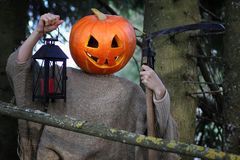 Horror pumpkin with a scythe Stock Photos