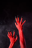 Horror red devil hands with black nails. On smoky background, studio shot royalty free stock images