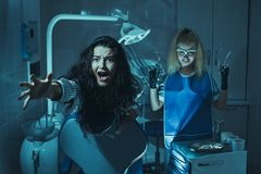 Horror scene in dentist office. Crazy evil stomatologist treating teeth to scared patient in dental chair. Mad maniac, murderer doctor stock image