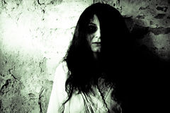 Horror scene of a scary woman. Portrait of a scary woman over old rustic wall stock photo
