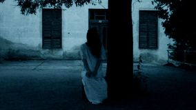 Horror scene of a scary woman. Horror movie scene of a scary woman. Woman siting under the tree stock footage