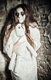 Horror scene: strange crazy girl with moppet doll in hands royalty free stock image