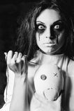 Horror scene: the strange crazy girl with moppet doll and needle. Horror scene: strange crazy girl with moppet doll and needle in hands. Closeup, black and white royalty free stock photo