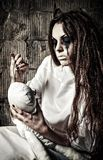 Horror scene: strange crazy girl with moppet doll and needle in hands Royalty Free Stock Photography