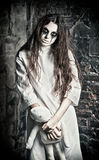Horror scene: strange mysterious girl with moppet doll in hands Royalty Free Stock Photography