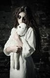 Horror shot: sad strange girl with moppet doll in hands Royalty Free Stock Photography