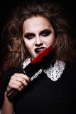 Horror shot: scary evil girl licking bloody knife Stock Photos