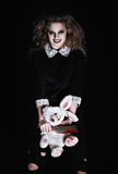 Horror shot: scary wicked girl with rabbit toy and bloody cleaver in hands Royalty Free Stock Photos