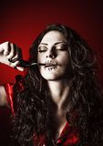 Horror shot: strange girl with mouth sewn shut cutting the thread Royalty Free Stock Images