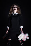 Horror shot: strange gothic girl with torn rabbit toy and bloody knife in hands Stock Images