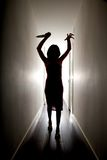 Horror silhouette with knife. Dark silhouette of woman with a big knife on her hand royalty free stock images