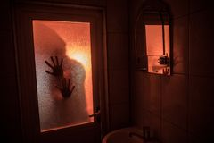 Horror silhouette of woman in window. Scary halloween concept Blurred silhouette of witch in bathroom. Selective focus royalty free stock photos