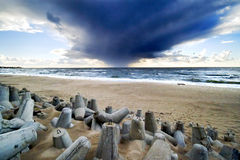 Horror sky and sea. A very dramatic stormy cloud coming from the sea, beach and protective stone blocks in the foreground Stock Photo