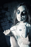 Horror style shot: scary crazy girl with moppet doll and needle in hands Royalty Free Stock Images