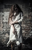 Horror style shot: scary monster girl with moppet doll in hands Stock Photo