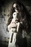 Horror style shot: strange sad girl with moppet doll in hands Stock Photography
