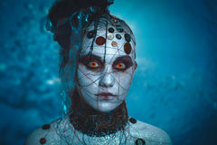Horror. Terrible dead women from a horror movie, creepy character with large bloody eyes, sewn buttons and hanging ropes. Dark blue background free place for Royalty Free Stock Photos