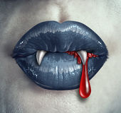 Horror Vampire Bloody Teeth. And fangs with a gothic style female with black lips and human liquid blood dripping from the mouth against ghost like white skin Stock Photography
