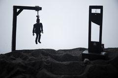 Horror view of hanged man on scaffold and Guillotine at misty evening with fog. Execution (or suicide) conceptual artwork. Decoration. Horror Halloween concept royalty free stock photo